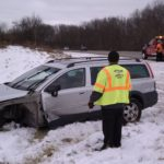 Car being pulled out of the median by a tow truck.