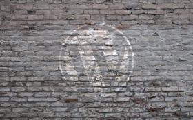 Large WordPress logo on grey brick wall